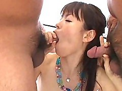 Pretty Asian girl takes turns sucking two dicks