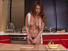 Hot and sexy redhead playing with a hard banana in the kitch