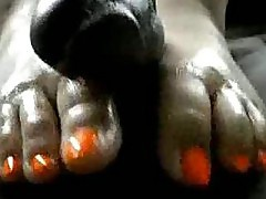 Asian babe gives an footjob to a black cock